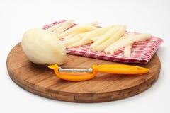 Rå potatisar för pommes frites och ett hjälpmedel för att skala Arkivbilder