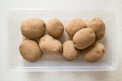 Rå potatisar i en plast- behållare Arkivbild