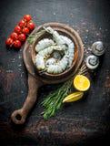 Rå räkor i en platta på en skärbräda med körsbärsröda tomater, rosmarin och snittcitronen royaltyfria foton