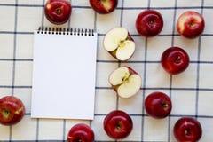 Rå röda äpplen och tom notepad på torkduken, bästa sikt Lägenhet som är lekmanna-, från över, över huvudet Utrymme för text fotografering för bildbyråer