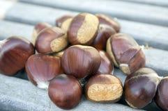 Rå söta kastanjer spridde på träsmakliga och sunda brunaktiga muttrar för tabell, Arkivfoto