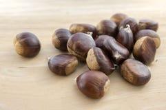Rå söta kastanjer spridde på träsmakliga och sunda brunaktiga muttrar för tabell, Arkivbild