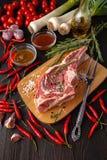 Rå saftiga köttbiffar som är klara för att grilla på ett svart kritabräde arkivbilder