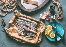 Rå sardiner på köksbordbakgrund med stekpannan och ingredienser för smaklig havs- matlagning arkivbild