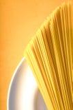 Rå spagetti på den vita plattan på den gula bakgrundslodlinjen royaltyfria foton