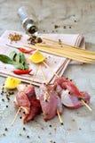 Rå steknålar av kött på tabellen Arkivfoto