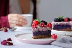 Rå strikt vegetariankaka med hallon och bluberries på den vita tabellen Royaltyfri Fotografi