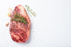 Rå striploinnötköttbiff med rosmarin, timjan, saltar och pepprar isolerat mot vit Bästa sikt med kopieringsutrymme arkivfoton