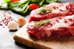 Rå svarta Angus Prime köttbiffar på träbräde royaltyfria foton