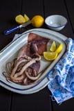 Rå tioarmad bläckfisk med citronkilar Arkivfoto