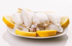 Rå tioarmad bläckfisk som är klar att lagas mat i platta och klippta citroner Royaltyfri Fotografi