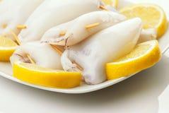 Rå tioarmad bläckfisk som är klar att lagas mat i platta och klippta citroner Royaltyfri Bild
