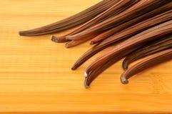 Rå vaniljböna på överkanten av träbrädet Arkivfoton