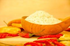 Rå vita ris inom den wood skeden tillsammans med röda kyla och biscu royaltyfri fotografi