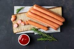 Rå wienerkorvkorvar med ketchup på skärbräda royaltyfri foto