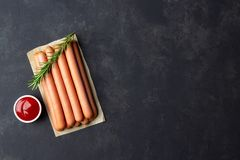 Rå wienerkorvkorvar med ketchup på skärbräda Top beskådar royaltyfri foto