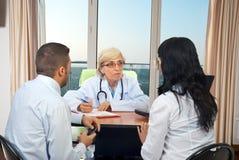 rådgivningpardoktorn ger läkarundersökning till Royaltyfri Foto
