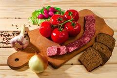 Rågbröd, korv, kött, skärbräda, rädisa, tomater, lökar, gräsplaner, vitlökört och kryddor på träbakgrund royaltyfria foton