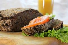 Rågbröd med grönsallat och tomaten på skärbrädan arkivbilder