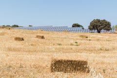 Rågfält med baler av batterier för hö och för sol- energi i Milos ö, Grekland arkivbilder