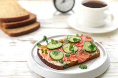 Rågsmörgås med laxen, gurkan, ostkräm och microgräsplaner Smaklig och sund frukost på tabellen Royaltyfria Foton
