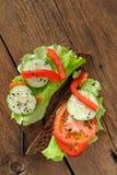 Rågsmörgås med salladsidor, tomat, gurka, spansk peppar på Arkivfoto