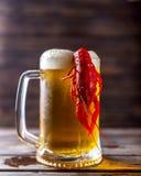 Råna av öl och kokta languster på en trätabell Arkivfoto
