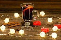Råna av funderat vin med kryddor, stearinljus i formen av en hjärta på en trätabell, en girland av lyktor Kanelbruna pinnar, anis Arkivfoto