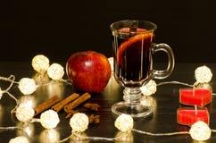 Råna av funderat vin med kryddor, stearinljus i formen av en hjärta, kanelbruna pinnar, stjärnaanis Arkivbilder