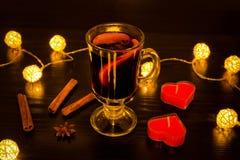 Råna av funderat vin med kryddor, stearinljus i formen av en hjärta, kanelbruna pinnar, stjärnaanis Belysning av rottinglyktor på Arkivfoton
