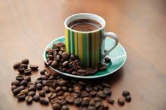 Råna av starkt kaffe på spridda kaffebönor Arkivfoton