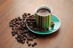 Råna av starkt kaffe på spridda kaffebönor Royaltyfri Foto