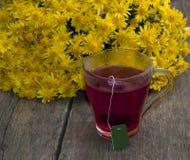 Råna av svart te mot en bukett av gula blommor Arkivbild