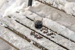 Råna av svarta espressokaffeställningar i snön, en träbänk fotografering för bildbyråer