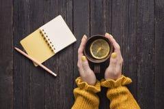 Råna av te med citronen i en kvinnlig hand, blyertspenna och notepad trä arkivfoto