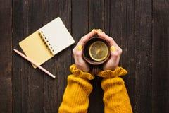 Råna av te med citronen i en kvinnlig hand, blyertspenna och notepad trä arkivbild