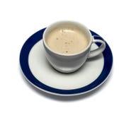 Råna från en cappuccino på ett tefat med en blå gräns Fotografering för Bildbyråer