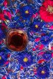 Råna med blommor för svart te och blått Arkivfoton