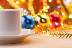 Råna med en kopp i den nya Year&en x27; s-tabell jullivstid fortfarande Nya Year& x27; s-leksaker på tabellen Royaltyfri Fotografi