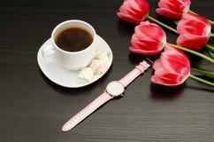 Råna med kaffe och marshmallowen, klockan, rosa tulpan svart tabell Top beskådar Arkivbild