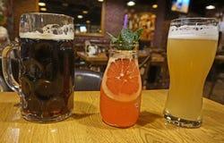 Råna med mörkt öl, en bank med en coctail och ett exponeringsglas med ett ljust öl på tabellen i baren royaltyfri foto