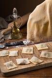 Råna mjöl, ägg, kavlen, olivolja i en krus på en träbakgrund som gör raviolit Arkivbilder