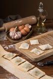 Råna mjöl, ägg, kavlen, olivolja i en krus på en träbakgrund som gör raviolit Royaltyfria Bilder
