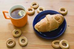 Råna mycket av svart te med citronen, gifflet på plattan och små baglar Arkivfoto