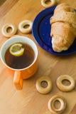 Råna mycket av svart te med citronen, gifflet på plattan och små baglar Arkivbilder