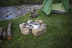 Råna ställningar på en journal nära branden på en campingplats arkivfoton