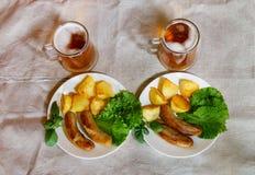 Rånar av öl med plattor av grillade korvar Top beskådar Royaltyfria Bilder