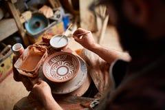 Rånar den likadana handgjorda keramikern för den läskiga framsidan på en trähylla, närbilden, shellowdjup av fältet royaltyfria bilder