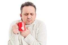 Rånar hållande te för den kalla mannen och frossa eller att frysa Arkivbilder