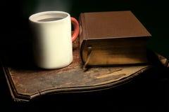 A rånar med kokhett te eller kaffe som förläggas bredvid en stor läder-destinerad bok, på en gammal och sliten trätabell royaltyfria bilder